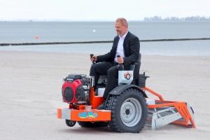 Oberbürgermeister Alexander Badrow überzeugt sich persönlich von der Leistungsfähigkeit der Strandreinigungsmaschine.